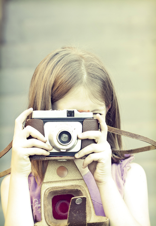 Little girl taking picture with old camera photo