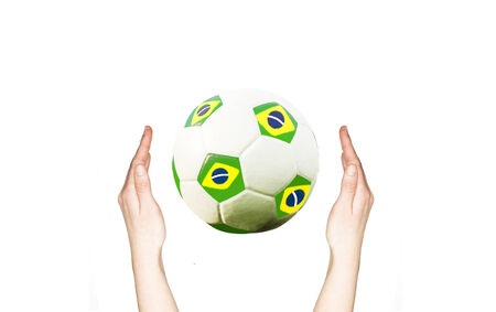 Hands holding soccer ball with the colors of Brazil flag photo