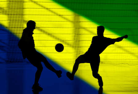 Silhouette of two man playing soccer and the colors of the Brazil flag photo