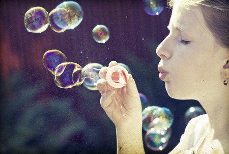 Retro styled photo of young girl blowing soap bubbles photo