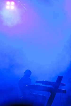 Musician on stage covered in smoke photo