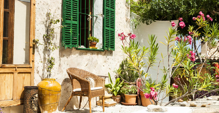 Traditional courtyard with chairs and a lot o flowers in old village in Mallorca island, Spain photo