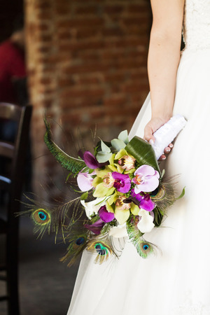 Bride holding beautiful wedding bouquet of orchid and calla photo