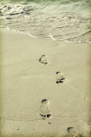 Footsteps in the sand on the beach photo