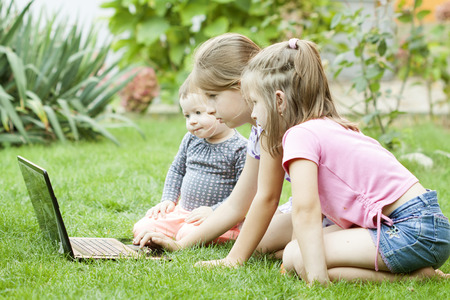jardin de infantes: Tres ni�os usando la computadora port�til en el jard�n