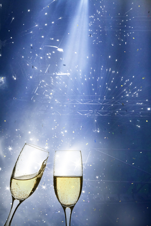 Glasses with champagne against fireworks and holiday lights photo