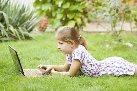 jardin de infantes: Ni�a que usa la computadora port�til en el jard�n