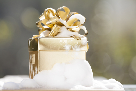 Golden Christmas background with present box on snow photo