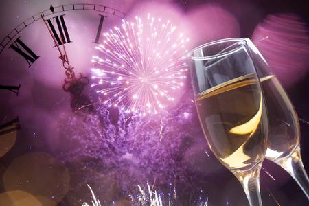Gläser mit Champagner gegen Urlaub Lichter und Uhr kurz vor Mitternacht Lizenzfreie Bilder