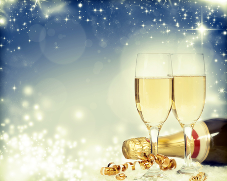 Glasses with champagne and bottle over sparkling holiday background photo