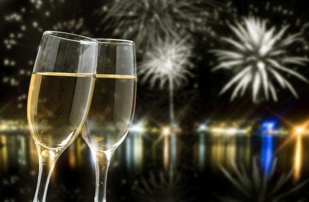 Glasses with champagne against fireworks photo