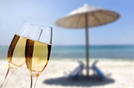 Nieuwjaar op het strand - Glazen champagne op het strand tegen de hemel en de blauwe zee