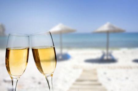 brindisi spumante: Capodanno in spiaggia - Bicchieri di champagne sulla spiaggia contro il cielo e il blu del mare