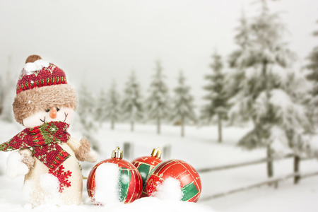 Snowman and red Christmas balls in the snow, snowy pine trees in the background photo