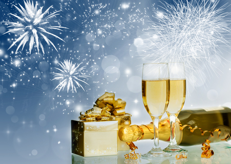 Glasses with champagne and bottle over fireworks and sparkling holiday background photo