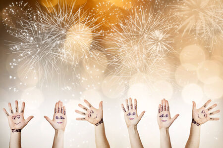 Painted hands with smiling faces celebrating New Year - New Year concept photo