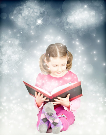 Happy child reading magic book - Christmas concept