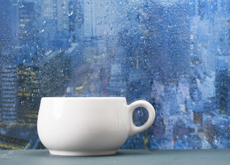 Coffee cup on a rainy day on window background