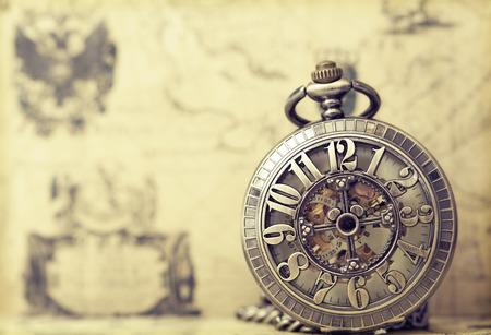 Vintage watch on antique map. Retro still life