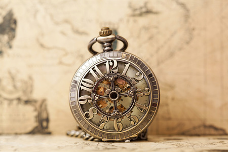 Reloj de la vendimia en el mapa antiguo. Aún vida retra Foto de archivo