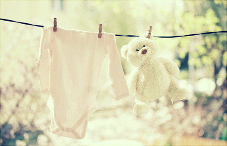 Baby clothes and teddy bear hanging on the clothesline Banque d'images