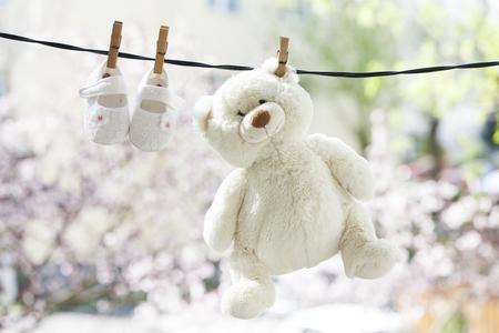 아기 옷과 테디는 빨랫줄에 매달려 곰