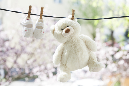 Baby clothes and teddy bear hanging on the clothesline Stockfoto