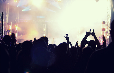 grunge music background: Cheering crowd in front of bright colorful stage lights - retro styled photo