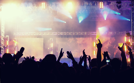Cheering crowd in front of bright colorful stage lights - retro styled photo
