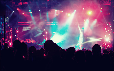 grunge music background: Cheering crowd in front of bright colorful stage lights  retro styled photo Stock Photo