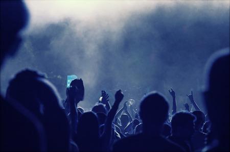 multitud: Muchedumbre que anima delante de luces del escenario de colores brillantes de estilo retro foto