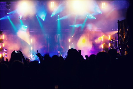 cheer full: Cheering crowd in front of bright colorful stage lights - retro styled photo