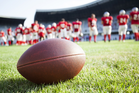 college football: Close up of an american football on the field, players in the background