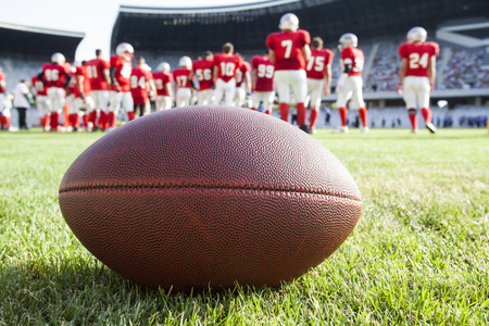 Close up of an american football on the field, players in the background