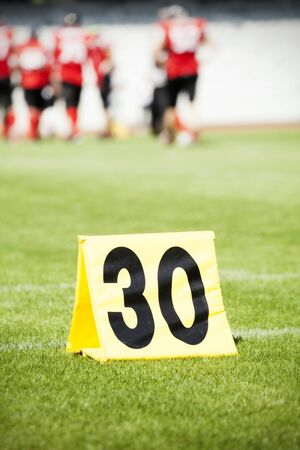 yard sign: Football yard line with a sign in the foreground Stock Photo