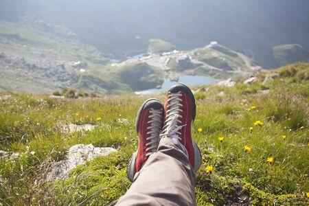 freedom: Legs of traveler sitting on a peak. Freedom concept