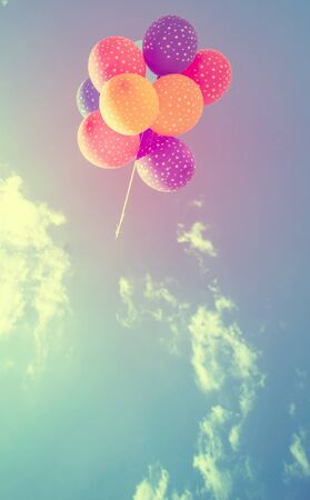 Colorful balloons on blue sky. Concept of love in summer, valentine, freedom, joy. Retro styled photo