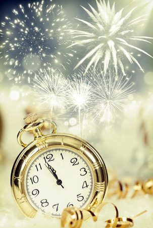 New Year's at midnight - Old clock with fireworks and holiday lights Foto de archivo
