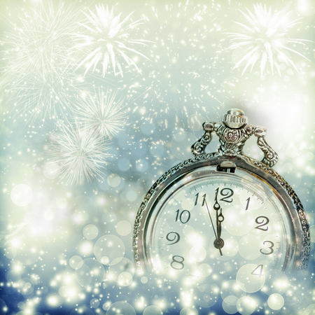 new years eve: New Years at midnight - Old clock with fireworks and holiday lights Stock Photo