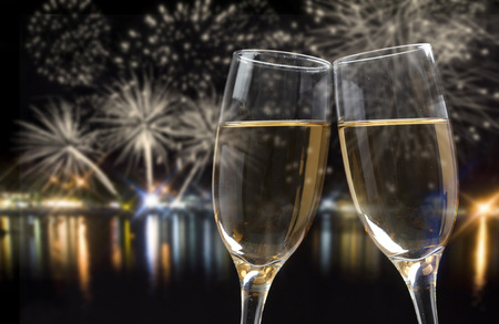 new: Glasses with champagne against fireworks and city lights