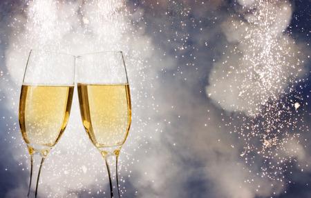 flauta: Gafas con champán sobre fuegos artificiales y brillante fondo de vacaciones