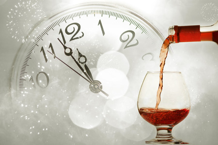 reloj: Pouring red wine against fireworks and clock close to midnight