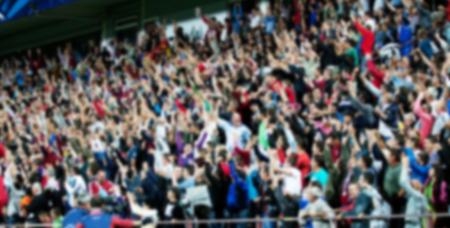 multitud de gente: Multitud de personas en un partido de fútbol - imagen borrosa
