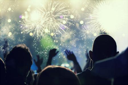 fuegos artificiales: Muchedumbre que anima y fuegos artificiales en la víspera de Año Nuevo - la gente celbrating en el aire abierto