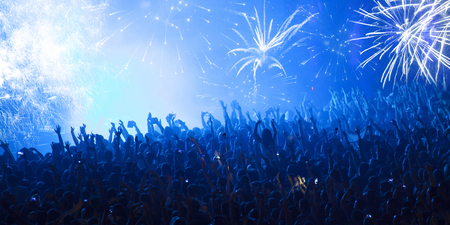 cheering crowd: Cheering crowd in front of bright colorful stage lights Stock Photo