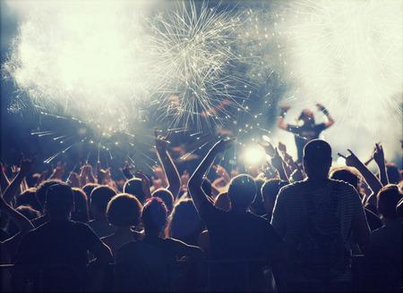 multitud: Muchedumbre que anima delante de brillantes luces de colores de la etapa Foto de archivo