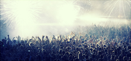 cheer full: Cheering crowd in front of bright colorful stage lights Stock Photo