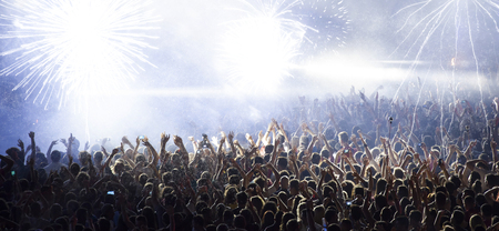 Cheering crowd in front of bright colorful stage lights Archivio Fotografico