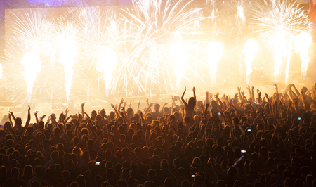 pyrotechnics: Cheering crowd at concert in front of stage with pyrotechnics Stock Photo