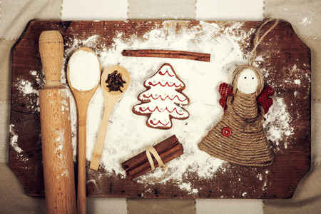 dessert table: Christmas background  with gingerbread cookies, spices and flour over wooden background